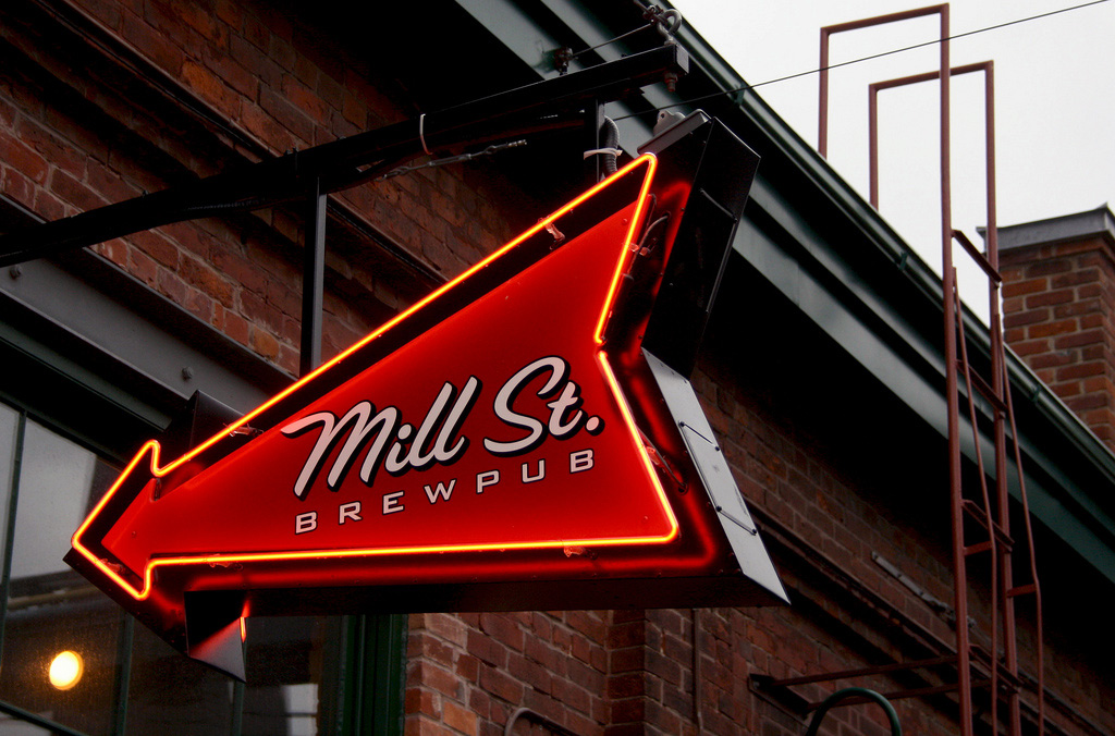 Outside a brick warehouse building, an arrow shaped neon sign will Mill St Brewery logo.
