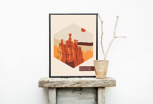 poster depicting a national park sitting on a rustic wooden table next to a plant holder
