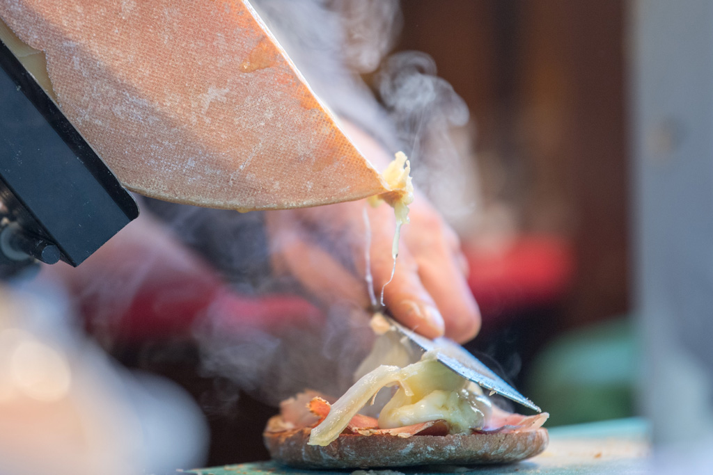 a chef scrapes cheese from a raclette wheel with a hot knife