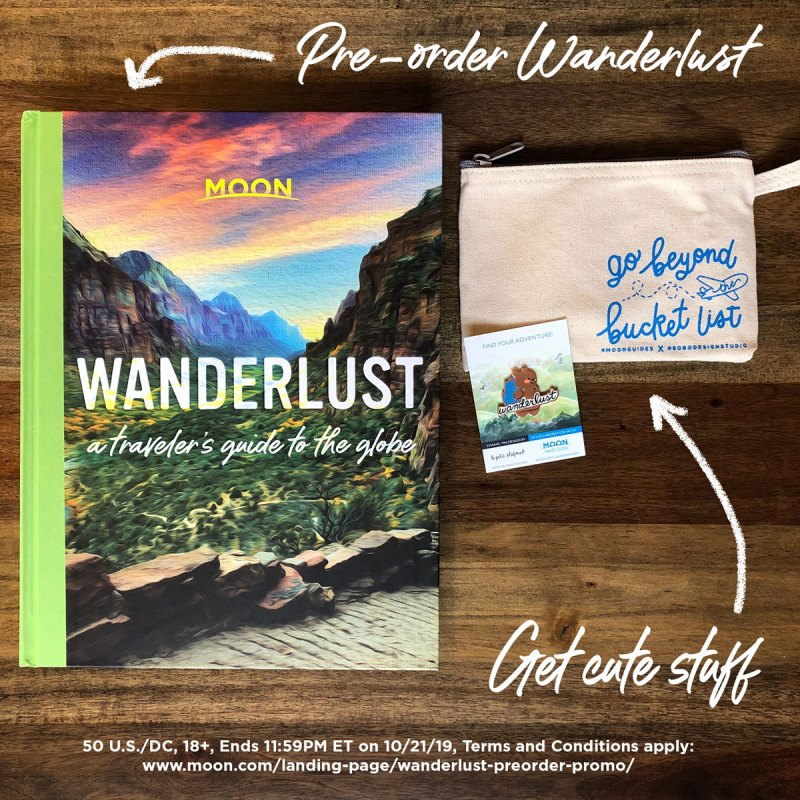 top down view of Wanderlust book with an enamel wanderlust pin and a canvas travel pouch